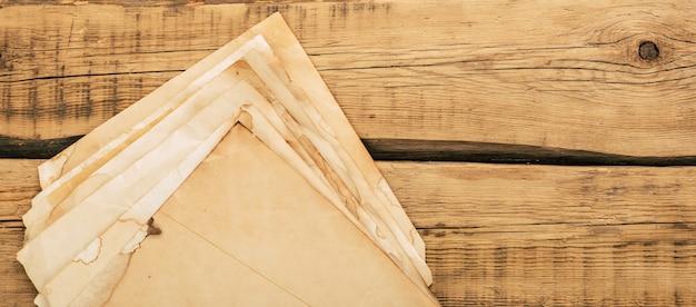 Blätter des alten weinlesepapiers auf einem holztisch. speicherplatz kopieren. hochwertiges foto