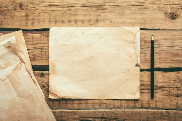 Blätter des alten weinlesepapiers auf einem holztisch. speicherplatz kopieren
