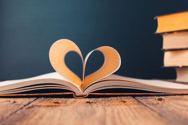Blätter eines notizbuchs in einem käfig in form eines herzens.
