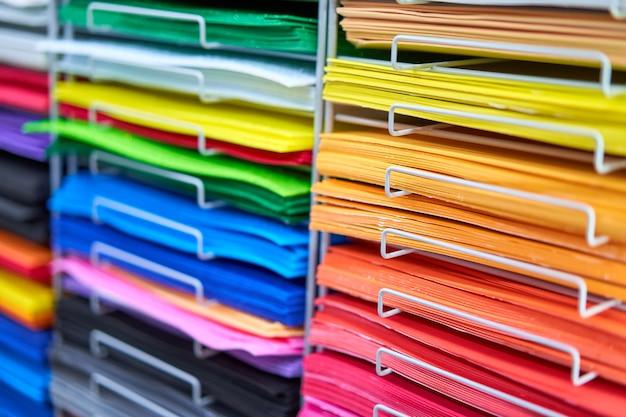 Blätter farbiger karton für kreative designerarbeiten. stapelt mehrfarbiges zeichenpapier im laden. bunte kunstdruckpapiere im regal zum verkauf schreibwarenladen