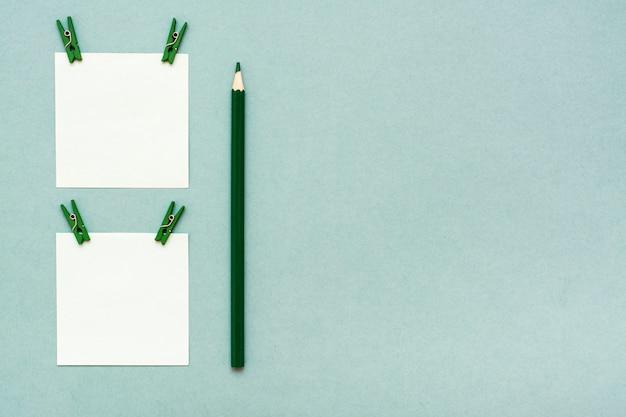 Blätter für notizen mit clips und einem bleistift auf einer grünen draufsicht