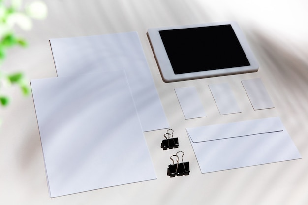 Blätter, geräte und arbeitsgeräte auf einem weißen tisch im innenbereich. kreativer, gemütlicher arbeitsplatz im home office, inspirierendes modell mit pflanzenschatten auf der oberfläche. konzept des remote-büros, freiberuflich, atmosphäre.