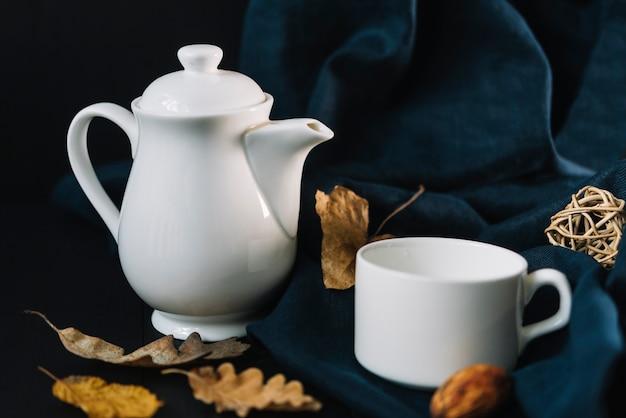 Blätter in der nähe von teekanne und tasse