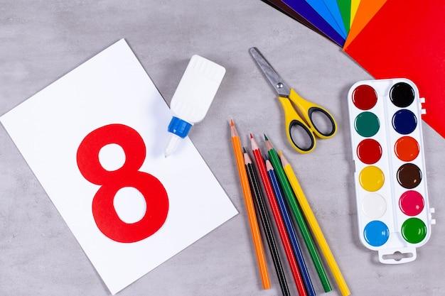 Blätter, kleber und schere auf einem tisch. 8. märz aus papier. kinderkunstprojekt, ein handwerk für kinder. basteln für kinder.