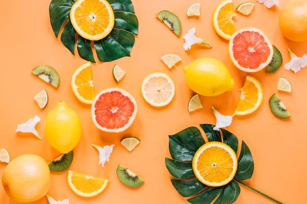 Blätter mit orangen in der nähe von früchten und blumen
