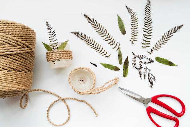 Blätter; schere; juteschnur und eingewickelte kerzen auf weißem hintergrund