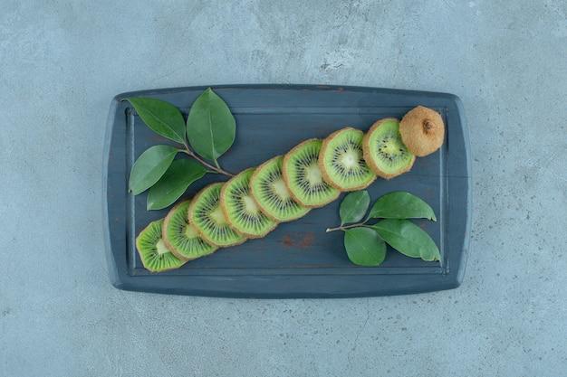 Blätter und geschnittene kiwi auf einem holztablett, auf dem marmorhintergrund. foto in hoher qualität