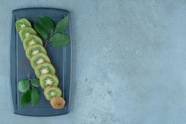 Blätter und geschnittene kiwi auf einem holztablett, auf dem marmorhintergrund.