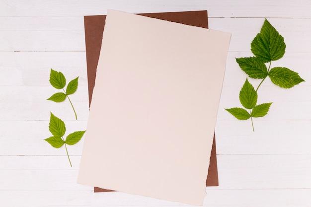 Blätter und papier auf hölzernem hintergrund