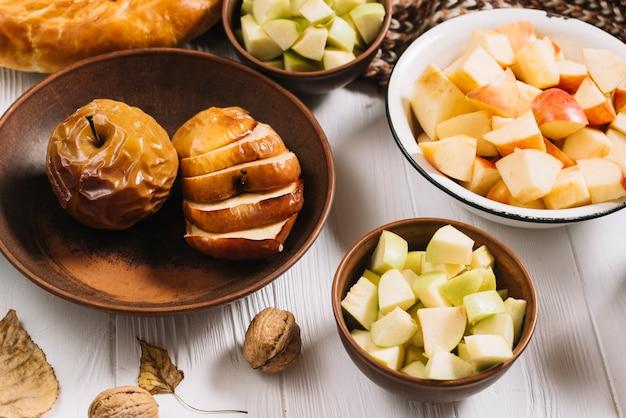 Blätter und walnuss in der nähe von gebackenen und geschnittenen äpfeln