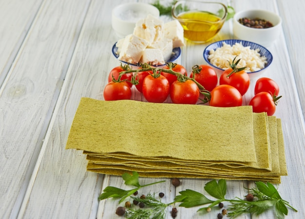 Blätter zum kochen von lasagne mit spinat, gestapelt in einem stapel und zutaten: kirschtomaten, käse, butter, pfeffer und kräuter. essen knollen.