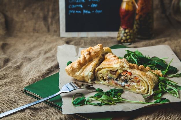 Blätterteig gefüllt mit fleisch, möhren, kartoffelkuchen, dekoriert mit rucola,