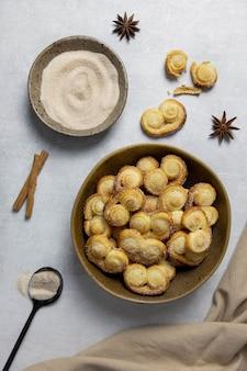 Blätterteigöse, palmier-kekse in einer schüssel mit zimt und zucker auf dem leichten beton.