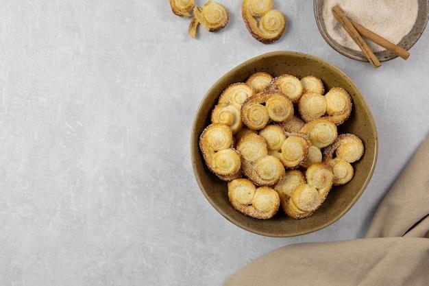 Blätterteigöse, palmier-kekse in einer schüssel mit zimt und zucker auf der hellen betonoberfläche