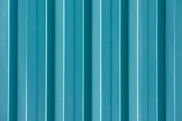 Bläulich feinkörnige betonwand in einem modernen stil mit weichem licht von links und vertikalem reliefdesign.