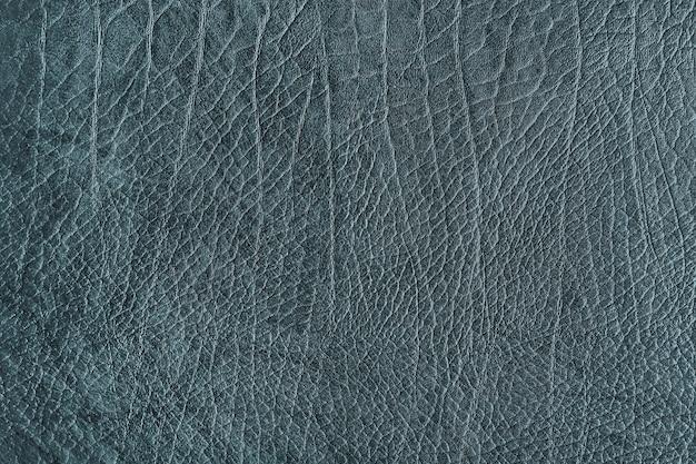 Bläulich-grauer strukturierter lederhintergrund mit falten