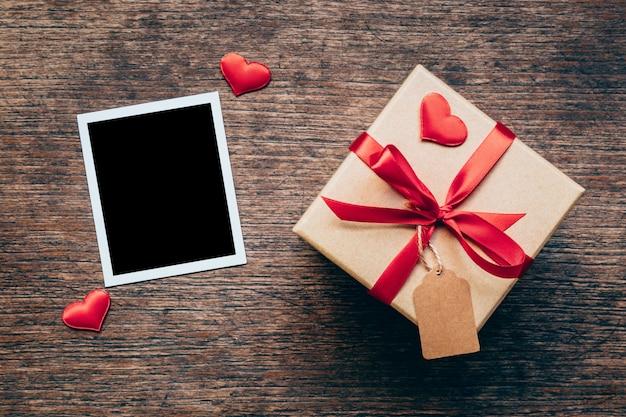 Blank bilderrahmen und geschenk-box mit roten herzen auf holz hintergrund.