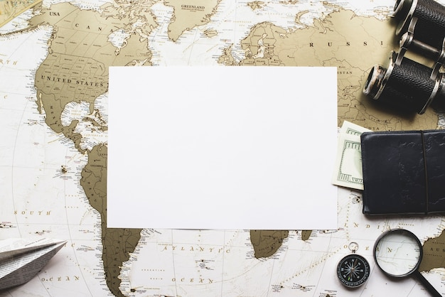 Blank papier mit reiseutensilien und weltkarte hintergrund