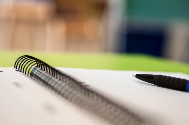 Blank scrapbook mit schule und bürobedarf auf bürotisch