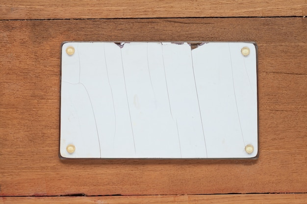Blanked und schmutziges fahrzeugkennzeichen auf hölzernem tabellenhintergrund.