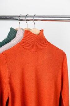 Blanko rollkragenpullover mockup auf kleiderbügel leuchtend orange ocker rollkragen mit beige und grün...