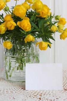 Blankokarte und gelbe frühlingsblumen in einer glasvase auf dem tisch