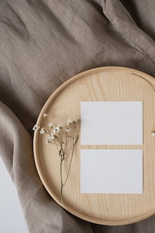 Blankopapier-blattkarten mit trockenblumen auf holzschatulle und grauer leinendecke