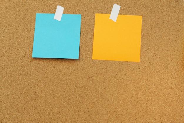 Blankopapier notizen auf kork bord kleben. kork-board mit leeren post-it. aufkleber leere notiz.