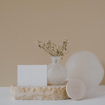 Blankopapierblattkarte mit blumen auf marmorstein gegen neutrale beige wand