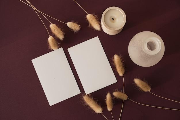 Blankopapierblattkarte mit kopienraum und kaninchenhasenschwanzgras mit sonnenlichtschatten auf burgund with