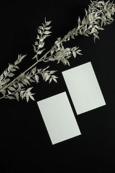 Blankopapierblattkarte mit mockup-kopienraum und trockenem blumenzweig auf schwarz