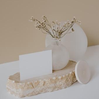 Blankopapierblattkarte mit mockup-kopierraum, trockenblumen, marmorstein gegen neutrale beige wand