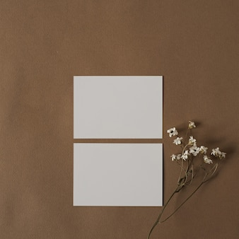 Blankopapierblattkarte mit schönen weißen blumen. ästhetische minimale geschäftsvorlage auf tiefem pastellbeigebraun