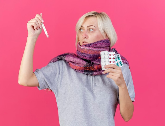 Blasse junge blonde kranke slawische frau, die schal trägt, hält packungen von medizinischen pillen