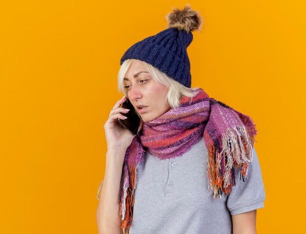 Blasse junge blonde kranke slawische frau, die wintermütze und schal trägt, spricht am telefon lokalisiert auf orange