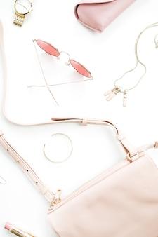Blasse pastellrosa weibliche zubehörkollektion auf weißem hintergrund. flacher lat, draufsicht auf sonnenbrille, clutch, halskette, armband, uhr