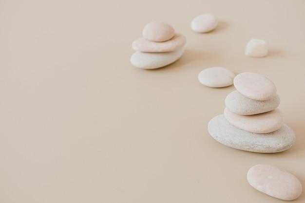 Blasse pastellsteine stapeln sich auf neutralen steinen. flache lage, draufsicht minimales spa-konzept.