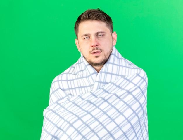 Blasser junger blonder kranker mann, der in plaid gewickelt steht, steht isoliert auf grüner wand