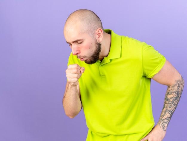 Blasser junger kaukasischer kranker mann, der auf purpur hustet
