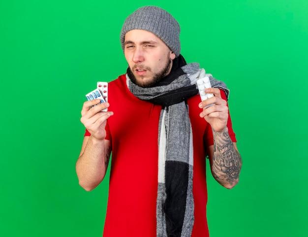 Blasser junger kaukasischer kranker mann, der wintermütze und schal trägt, hält packungen der medizinischen pillen auf grün