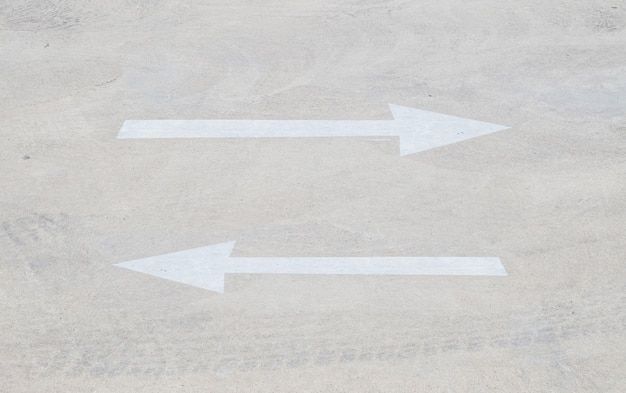 Blasses pfeilzeichen der nahaufnahme auf zementboden im parkplatz