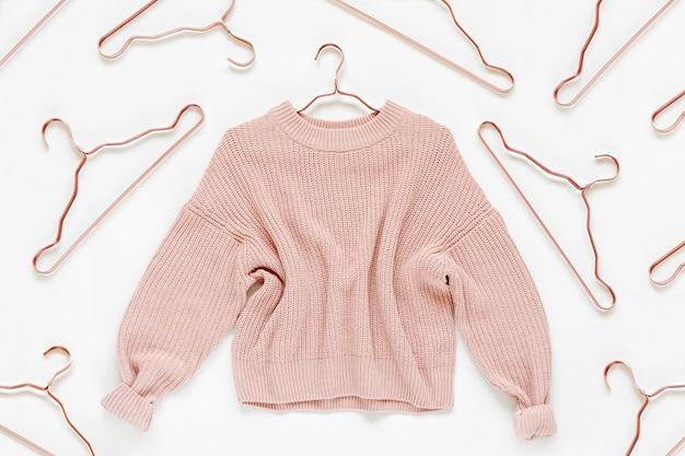 Blassrosa strickpullover mit metallischen kleiderbügeln auf weißem hintergrund. herbst- und winterkleidung. shop, verkauf, modekonzept.
