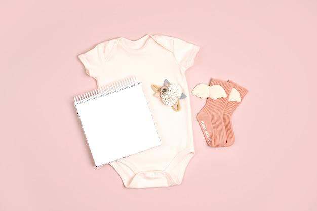 Blassrosa süßer babybody mit mock-up-karte. set kinderkleidung und accessoires. mode neugeborenes. flache lage, ansicht von oben