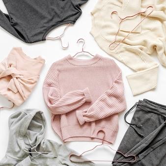 Blassrosa warmer pullover, graue hosen und andere kleidung. herbst- oder winteroutfit für damen. flache lage, ansicht von oben.