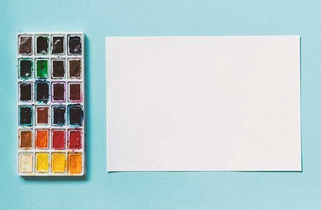 Blatt aquarellpapier und palette von aquarellen
