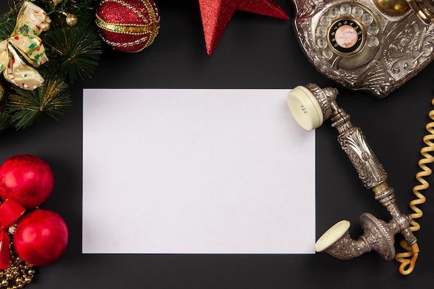 Blatt des weißen papiers mit weinlese-telefon auf weihnachtshintergrund-draufsichtmodell