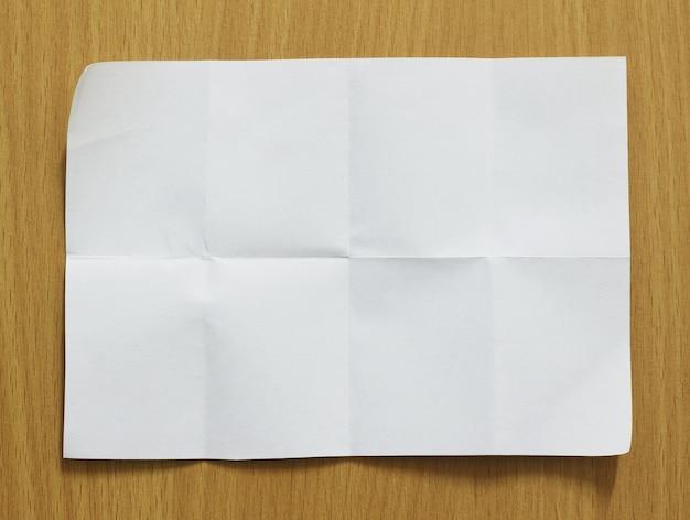 Blatt papier auf holzhintergrund