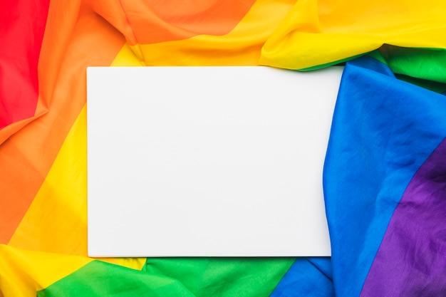 Blatt papier auf mehrfarbiger flagge