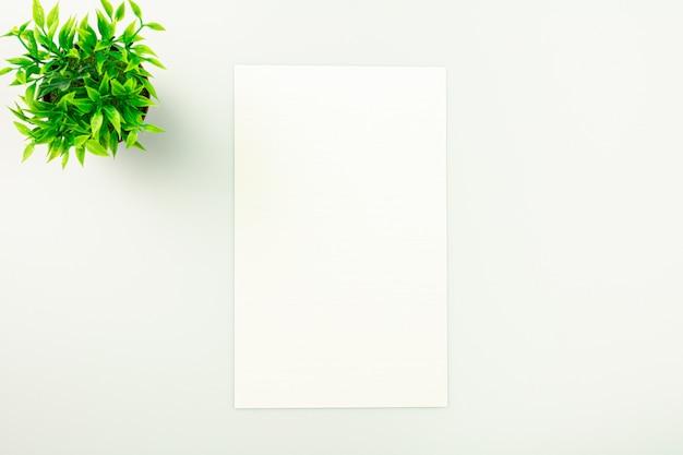 Blatt papier auf weißem schreibtischhintergrund mit kopie.