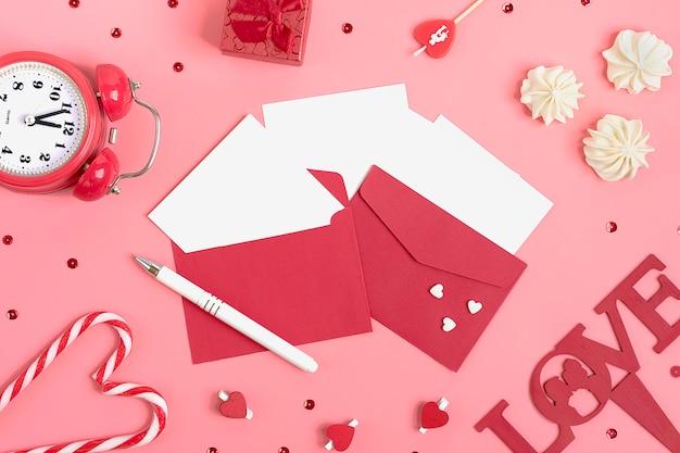 Blatt papier für nachricht, baiser, roter umschlag, geschenkbox, stift, uhr, kerze. valentinstag